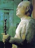 Houten beeld van een man met stok.