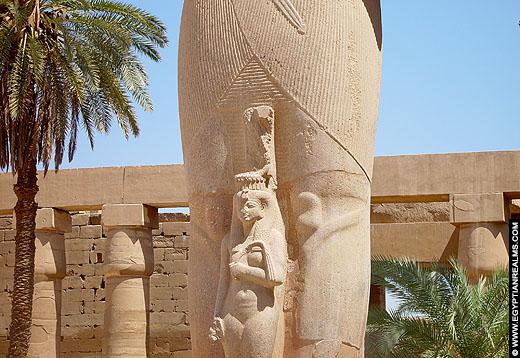 De koningin poseert voor een beeld van de koning in de Karnak Tempel.