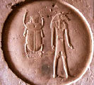 Ancient Egyptian hieroglyph sundisc with scarab and Khnum